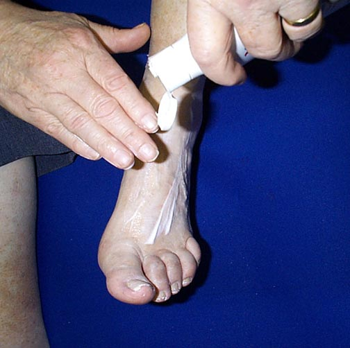 Photo of person applying lotion to feet