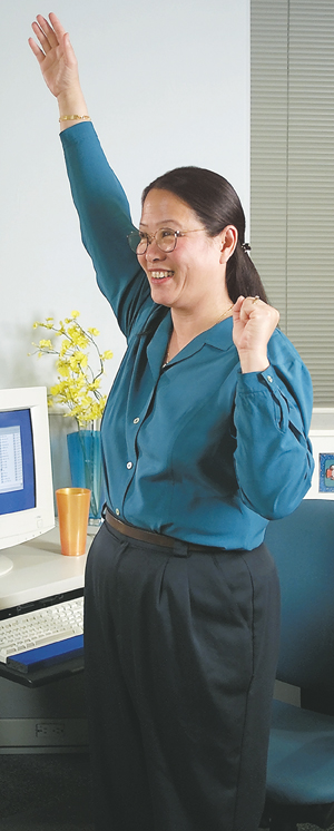 Person standing at workplace desk, back straight, stretching one arm straight above head.