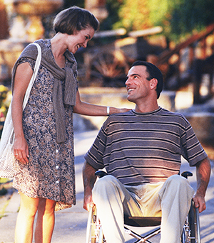 Woman and man in wheelchair taking walk outdoors and talking.