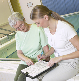 Physical therapist sitting with senior woman looking at exercise sheet.