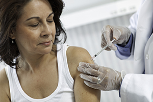 Woman getting vaccine shot by health care provider.