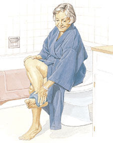 Woman in robe sitting in bathroom, drying foot with towel.