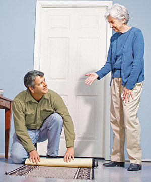 Younger man rolling up throw rug for older woman.