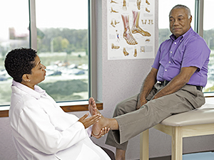 Healthcare provider examining the foot of a patient sitting on an exam table.