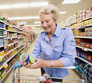 Woman reading food label on can in grocery store.