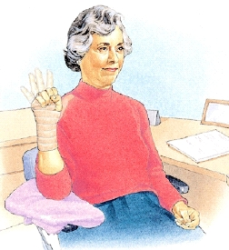 Woman with bandaged wrist sitting arm bent and elbow supported on pillow. She is opening and closing fist on bandaged arm.