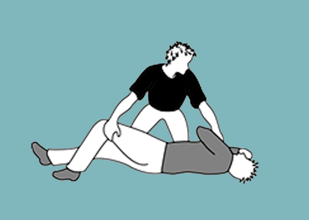 Person moving unconscious man's knee and shoulder to position him on his side.