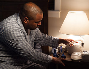 Man sitting on bed, preparing CPAP mask and machine.