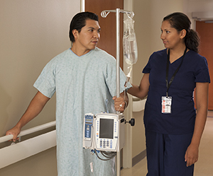 Healthcare provider walking with man in hospital hallway.