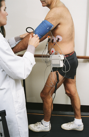 Man with wires attached to chest walking on treadmill. Wires go to ECG machine next to treadmill. Healthcare provider is monitoring ECG machine.