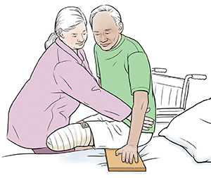 Healthcare provider helping man with amputated leg to use slide board from wheelchair into bed.