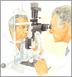 Man sitting in front of eye exam scope. Man's chin is resting on support. Healthcare provider is sitting on other side of scope, looking through eyepieces to examine man's eyes.
