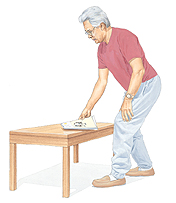 Man facing coffee table and bending at knees to pick up magazine.