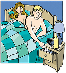 Woman and man lying in bed. Man is reaching for condom in bedside table drawer.