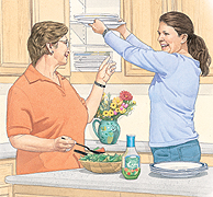 Older woman making salad in kitchen. Young woman reaching into upper cabinet to remove plates.