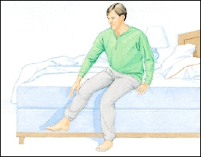 Man sitting at edge of bed preparing to stand up.