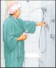 Woman in robe turning on water in shower. Shower chair is in shower stall. Grab bar and handheld showerhead are installed.
