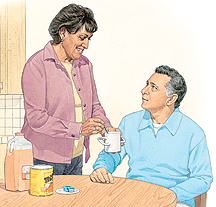 Woman handing man cup of orange juice. Bottle of orange juice and can of powder are on table.