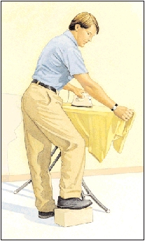 Man ironing shirt with one foot raised on low footrest.