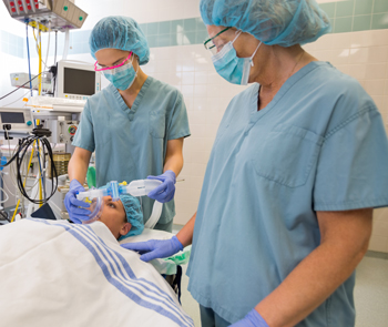 Anesthesia specialist placing an oxygen mask on a female patient in an operating room.